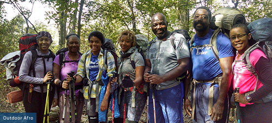 A group of African American hikers stand together with their large hiking packs with a dense forest behind them, smiling for the picture