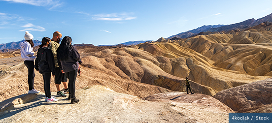 A small group of hikers stand on a peak overlooking many ridged peaks in Death Valley National Park