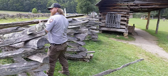 Darin Brinkmeyer places a log on top of a split-rail fence, a log cabin structure can be seen behind him