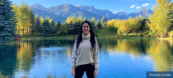 Richelle stands in front of a scenic lake lined with evergreen and aspen trees, a line of mountains can be seen in the distance