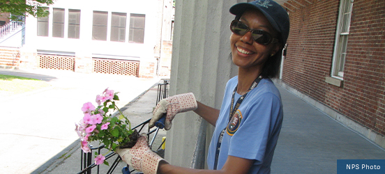 A volunteer smiles for the picture while holding a flowering plant and a trowel above a flower box at Governors Island National Monument