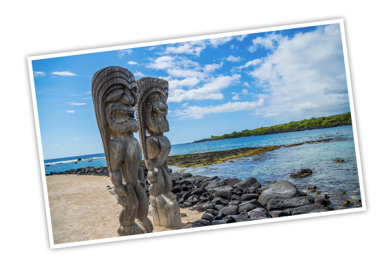 Two carved, wooden statues, known as Ki'i, on the beach with the blue ocean and a lush, green island behind them