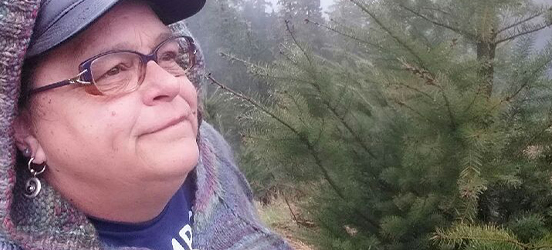 A close up image of Gail Heine as she looks off into the wilderness, evergreen trees fill the background behind her