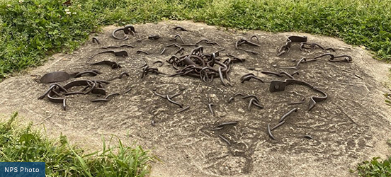 Broken metal shackles are embedded in the hard, dirt ground at Natchez National Historical Park
