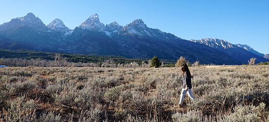 Ashley walks through open grassland with the mountains of Grand Teton National Park behind her
