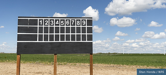 A blank baseball scoreboard on wooden posts stands in front of an open grass field