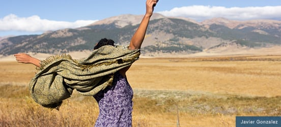 A Black woman raises her arms while standing in a dry, grass field with mountains in the distance