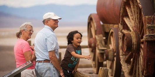 A child leans against an exhibit fence, pointing towards the historic wagon in front of him while two adults look in the direction he's pointing