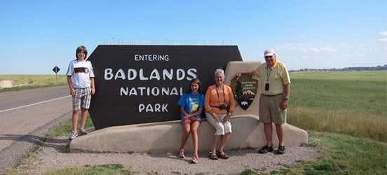 The Smith-Grey family of four pose in front of the parkk entrance sign at Badlands National Park