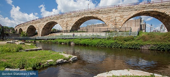 A stone bridge runs along the river with many pedestrian walk ways at Mill Ruins Park in downtown Minneapolis