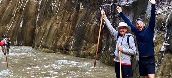 Eric and his dad stand in the water at Zion Narrows with the arms raised in celebration