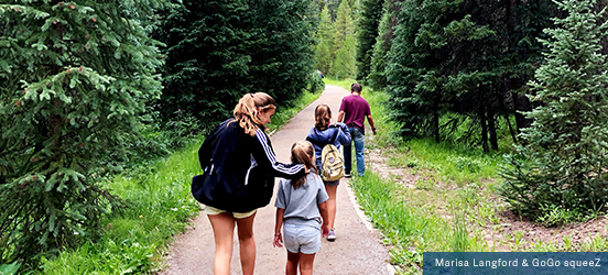 A family walks down a paved trail through a lush forest of evergreen trees
