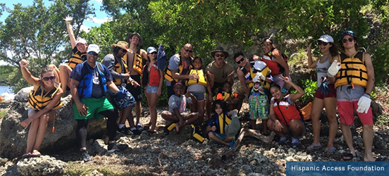 A large group of people outfitted in swimming gear and life vests pose on a rocky shore for the picture