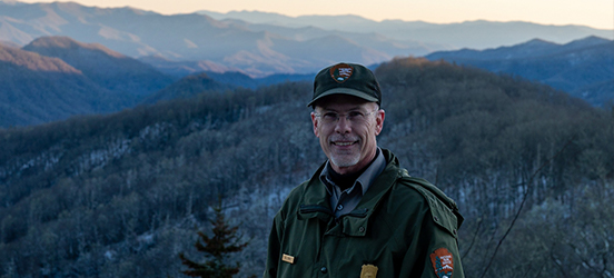 Bill Stiver smiles in his NPS uniform at the top of a mountain, an incredible view behind him of rolling, snow dusted, blue-toned mountains in Great Smoky Mountains National Park