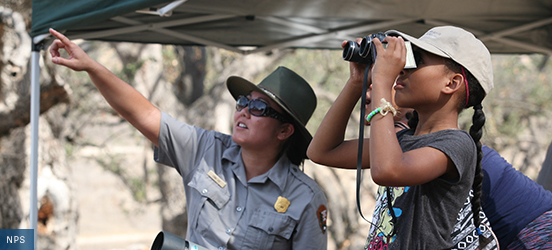 A park ranger points to the distance as a child looks through binoculars in the same direction at Santa Monica Mountains National Recreation Area