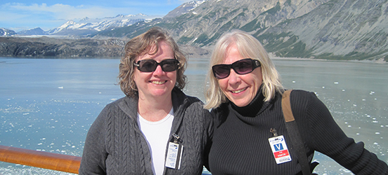 Maureen O'Leary and Mary Pat Gallagher smile together for their picture on the deck of a boat with the blue water and mountains of Glacier Bay National Park & Preserve behind them