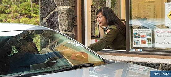 A park ranger leans through a drive-up window to check a visitor's park pass as they drive into a park