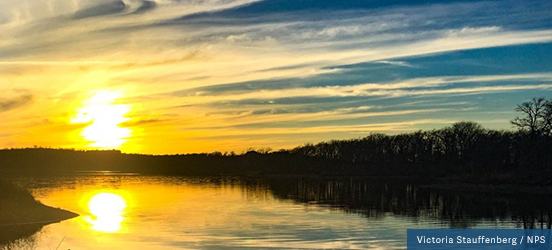 A bright yellow sun sets on the river in Chickasaw National Recreation Area