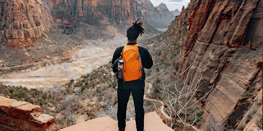 A person stands at a lookout point while hiking to Angel's Landing in Zion National Park