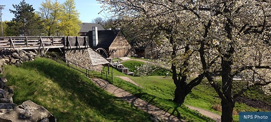 A view of the Mill at Saugus Iron Works National Historic Site, surrounded by small, rolling, grassy hills and flowering trees