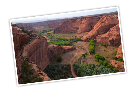 Red rock forming a deep, but wide canyon as far as the eye can see and bright green trees dotting the canyon floor, outlining the flowing river, snaking its way to the horizon at Canyon de Chelly National Monument