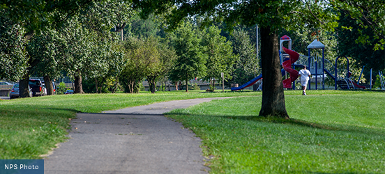 A jogger runs along a paved path through grassy areas and past a playground in Anacostia Park