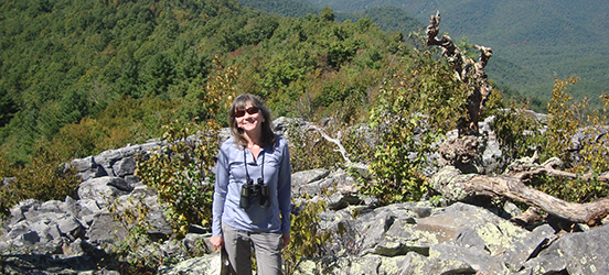 Donna Boone smiles for the picture at a mountain top with a beautiful view of tree-covered mountains behind her