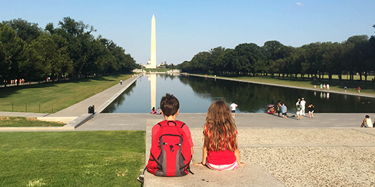Two children sit on the steps of the Lincoln Memorial, looking out at the Washington Monument
