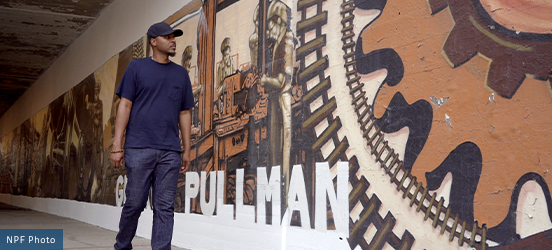 Artist Joe Nelson walks beside a huge mural depicting the historic labor work that was done at  Pullman National Monument