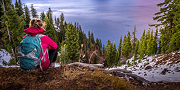 young woman sits on the ground overlooking Crater Lake