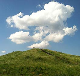 large white cloud over the top of a grassy mound in poverty point national monument