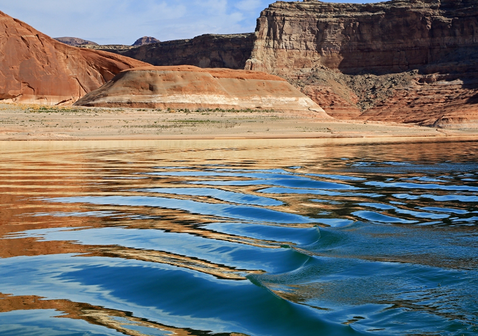 Ripples in the lake reflect the sandstone cliffs