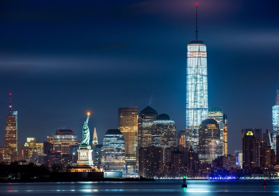 The New York City skyline at night, including the Statue of Liberty.