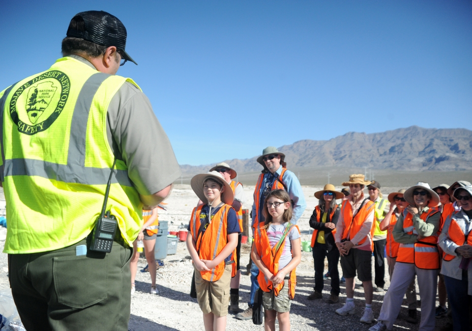 A group of children are led by a ranger in a paleontology demonstration at Tule Springs Fossil Beds National Monument