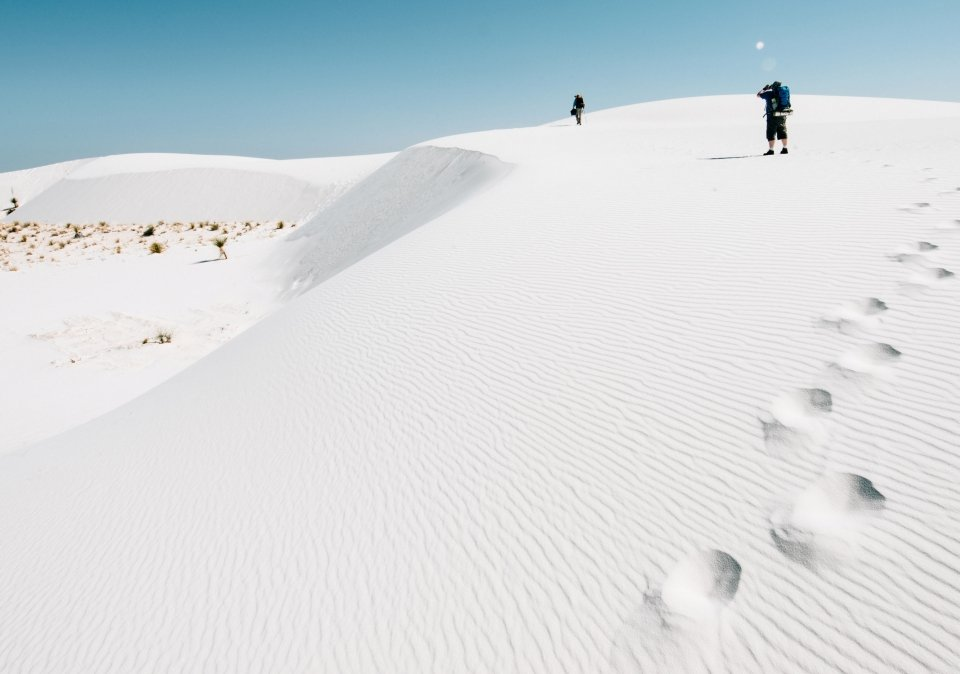Intrepid hikers make their way across the dunes in White Sands