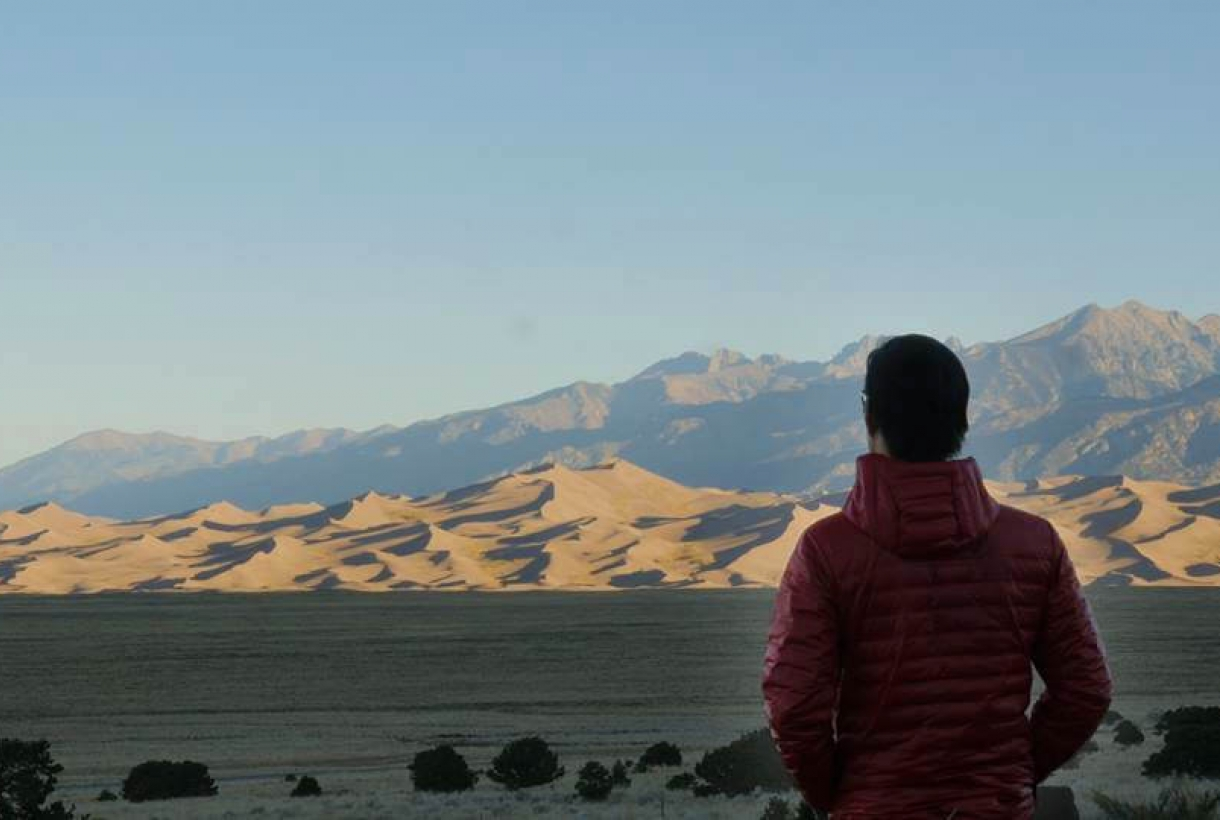 Back of Andrew Lin looking out over the sun-lit Great Sand Dunes National Park and Preserve