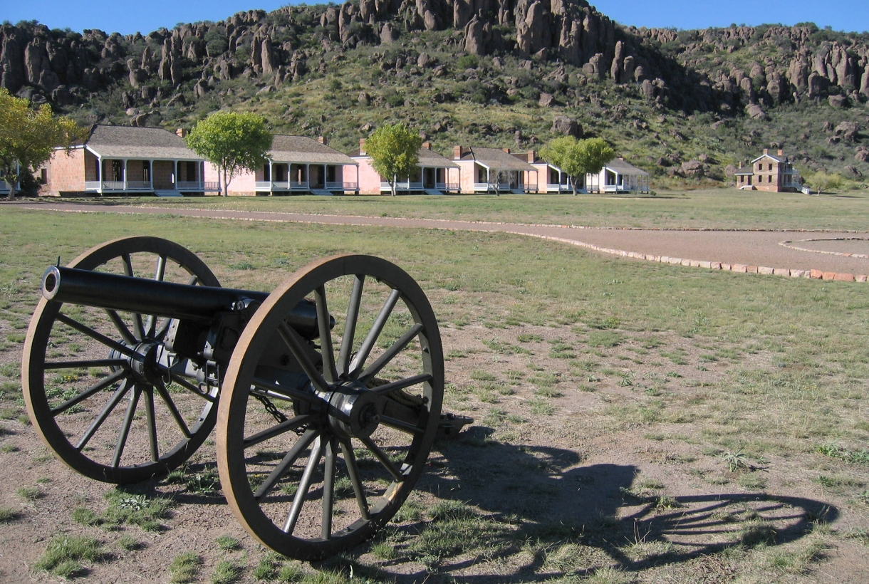 A cannon in a field near mountains