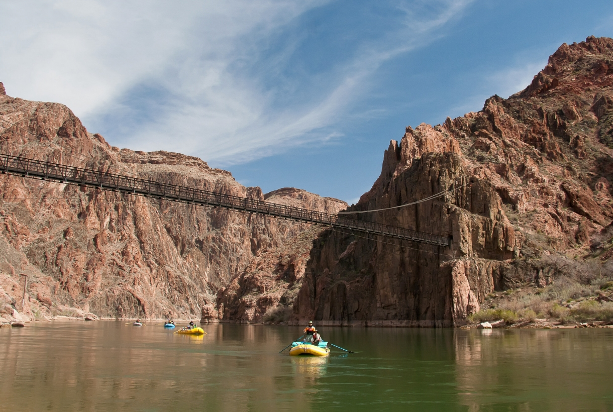 4 rafts paddling down the Colorado River through Grand Canyon National Park