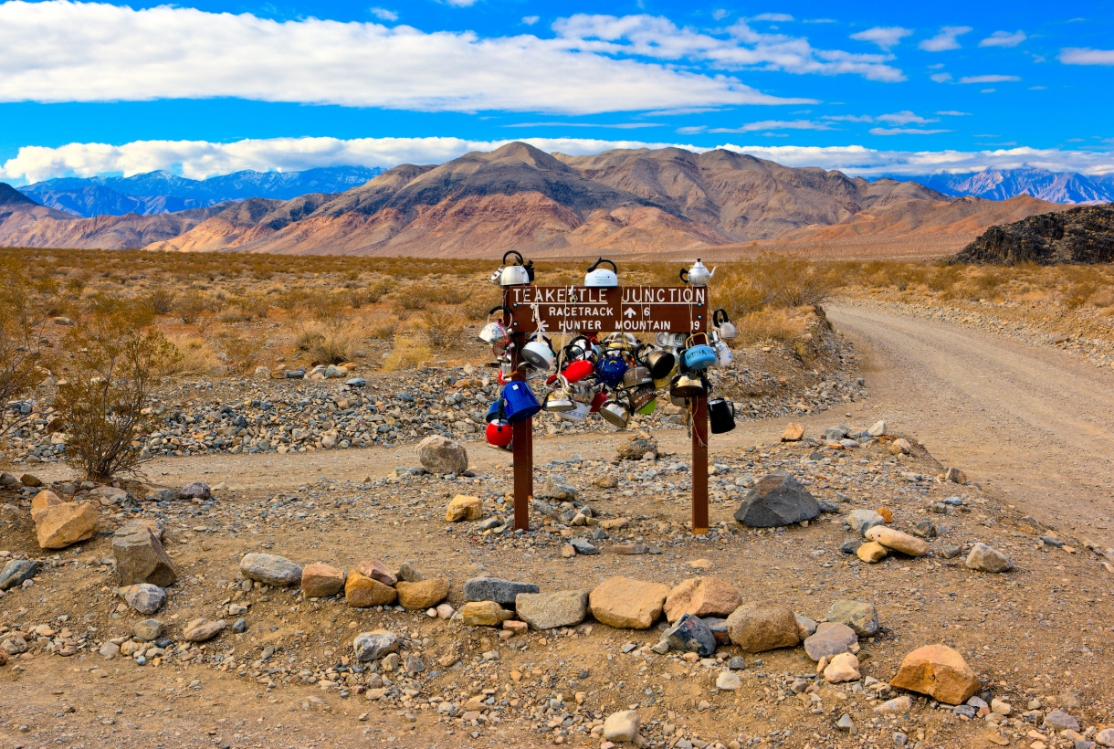 Photo of Teakettle Junction sign with with tea kettles hanging off of it