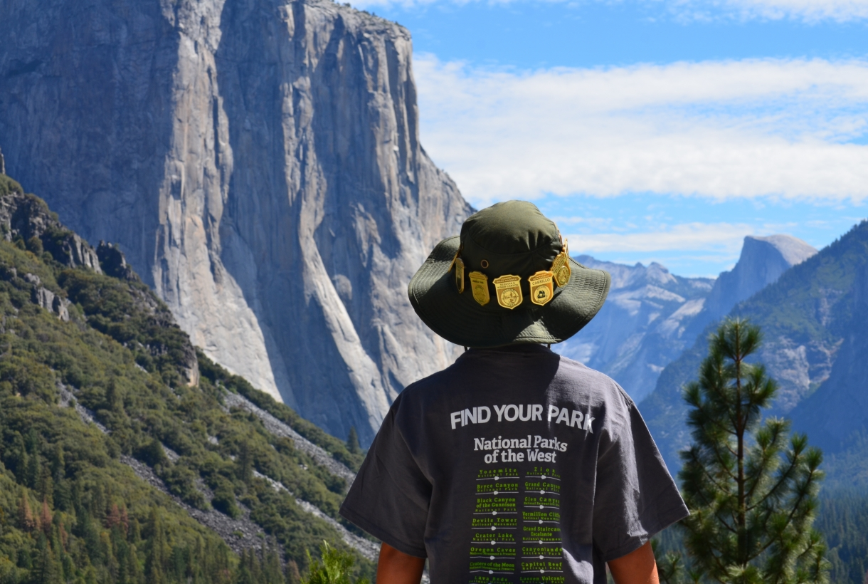 Back of a person wearing a Find Your Park shirt and a hat in Yosemite