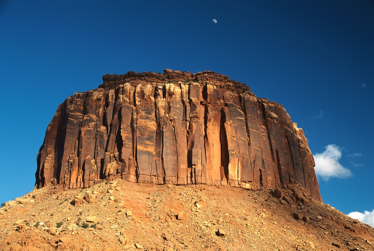 Pillar of red and black sandstone rock jutting out of a rocky terrain at Canyonlands