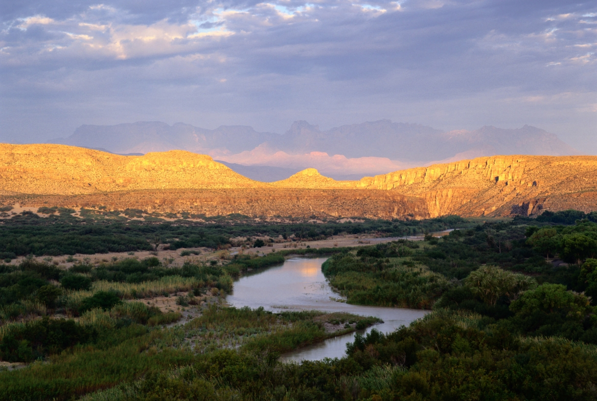 A river running through a grassy plain with sun-lit mountains in the background at Big Bend