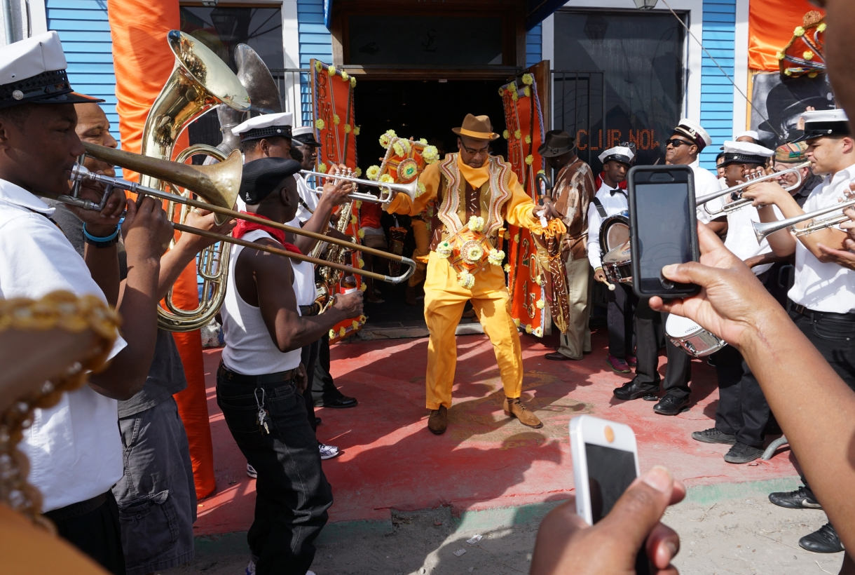 African American man dressed in a yellow suit with a brass band playing around him.