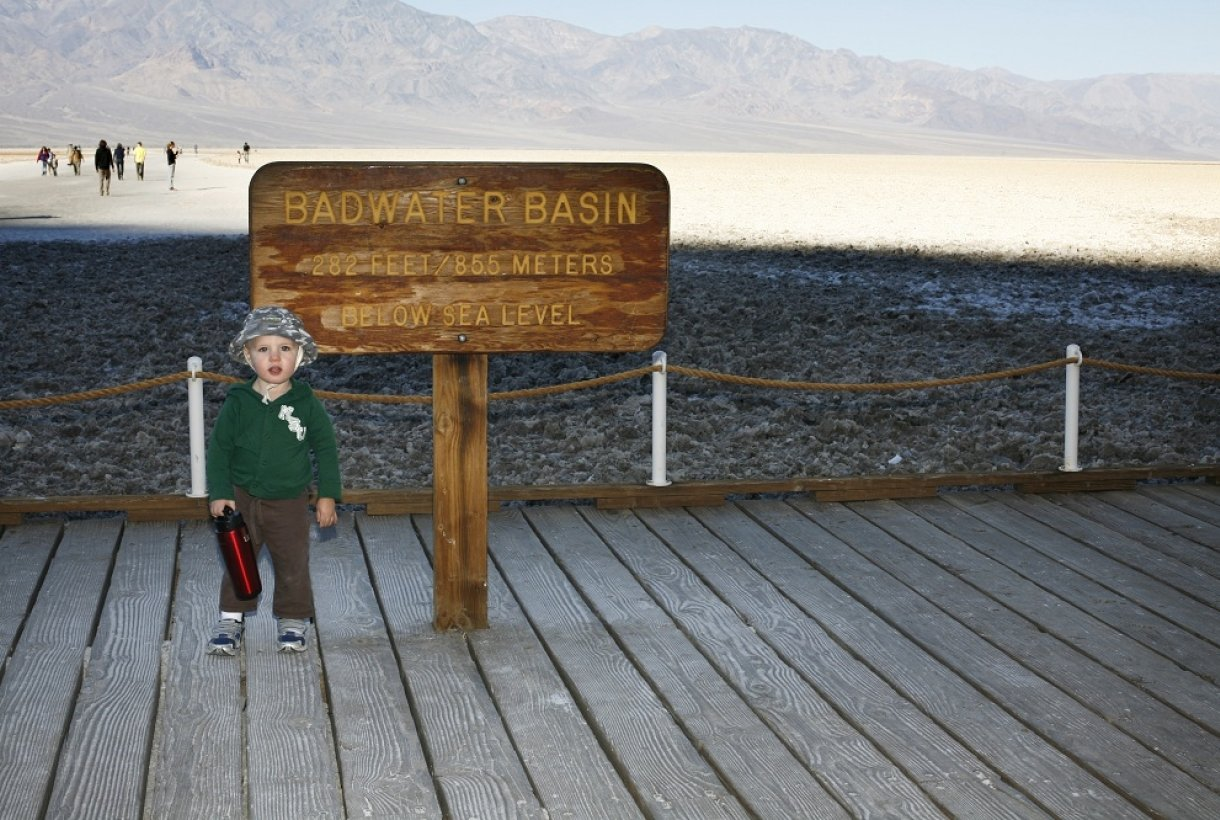 Toddler standing in front of Badwater Basin sign