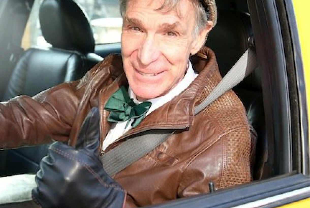 Bill Nye sitting in driver's seat of car, giving thumbs up