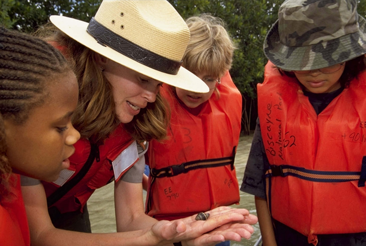 A park ranger shows a small hermit crab to three young visitors in orange lifevests