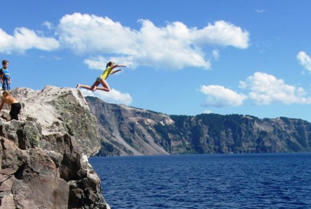 Young girl jumping into the deepest lake in the U.S. at Crater Lake National Park