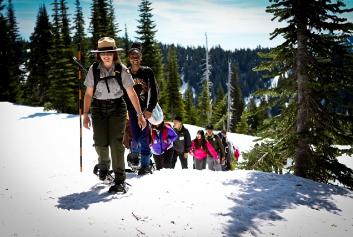 Park ranger and students hiking through snow at Klondike Gold Rush National Historical Park