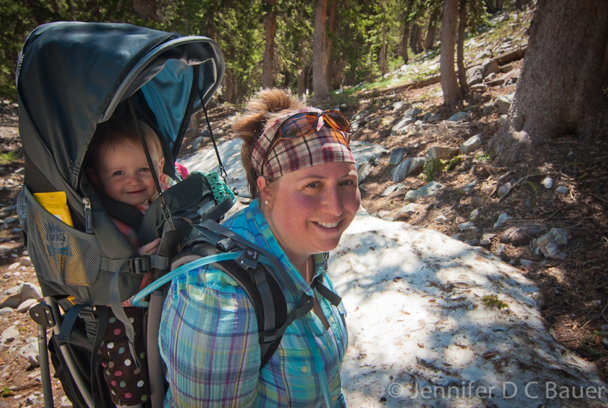 Mom Carrying Child Hiking in Park
