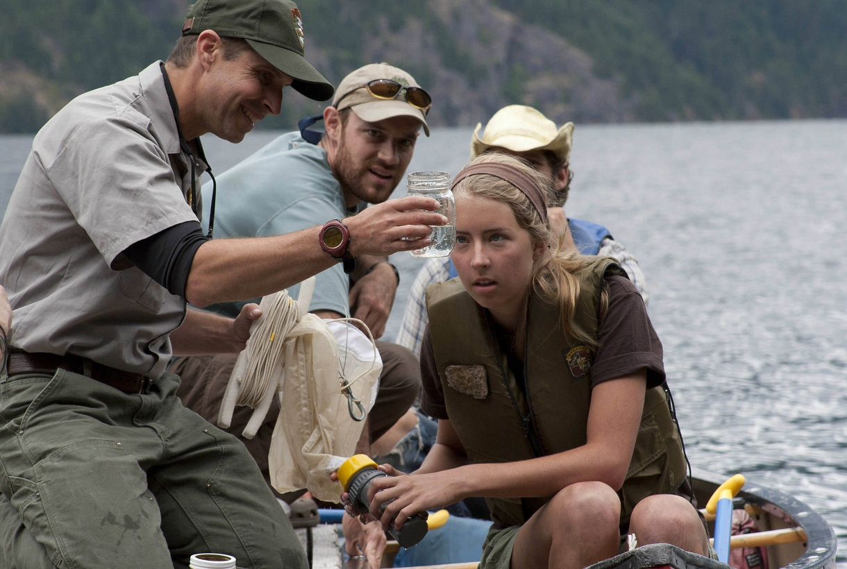 An NPS park ranger shows a student a jar of water on a canoe